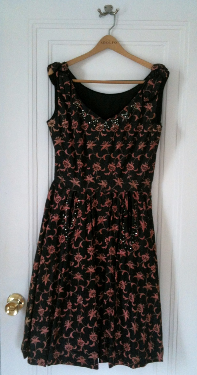 It may not look like much on a hanger, but this 1950's dress is gorgeous. The pattern you see is embroidered on while the neckline & pockets are piped in velvet. Usually I'm not a fan of sparkly shineys on my clothing, but the studs on this dress help make it special & add to its beauty. I can't wait until I'm unpacked so I can finally wear this lovely dress at my fancy pants housewarming party.